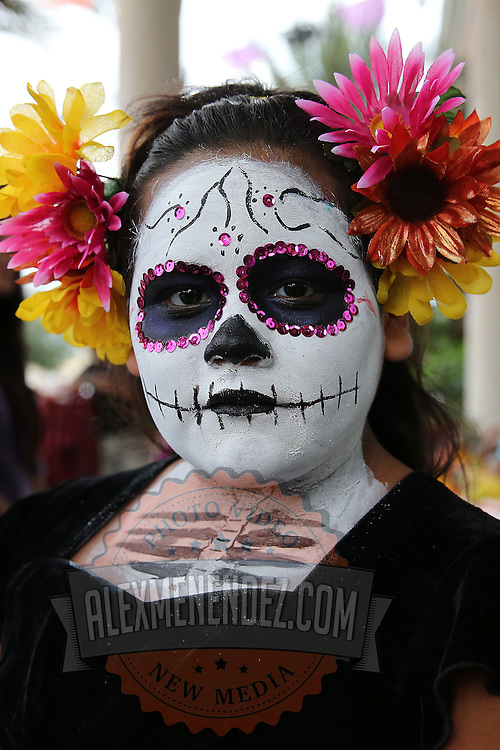 """The celebration of Day of the Dead or """"Día de los Muertos"""" at the Mexican Consulate in Orlando, Florida on Saturday, November 2, 2013. Dia de los Muertos is a Latin holiday celebrating friends and family members who have died. Traditions include building private altars called ofrendas to honor the deceased using sugar skulls, marigolds, and the favorite foods and beverages of the departed and visiting graves with these as gifts. (AP Photo/Alex Menendez)"""