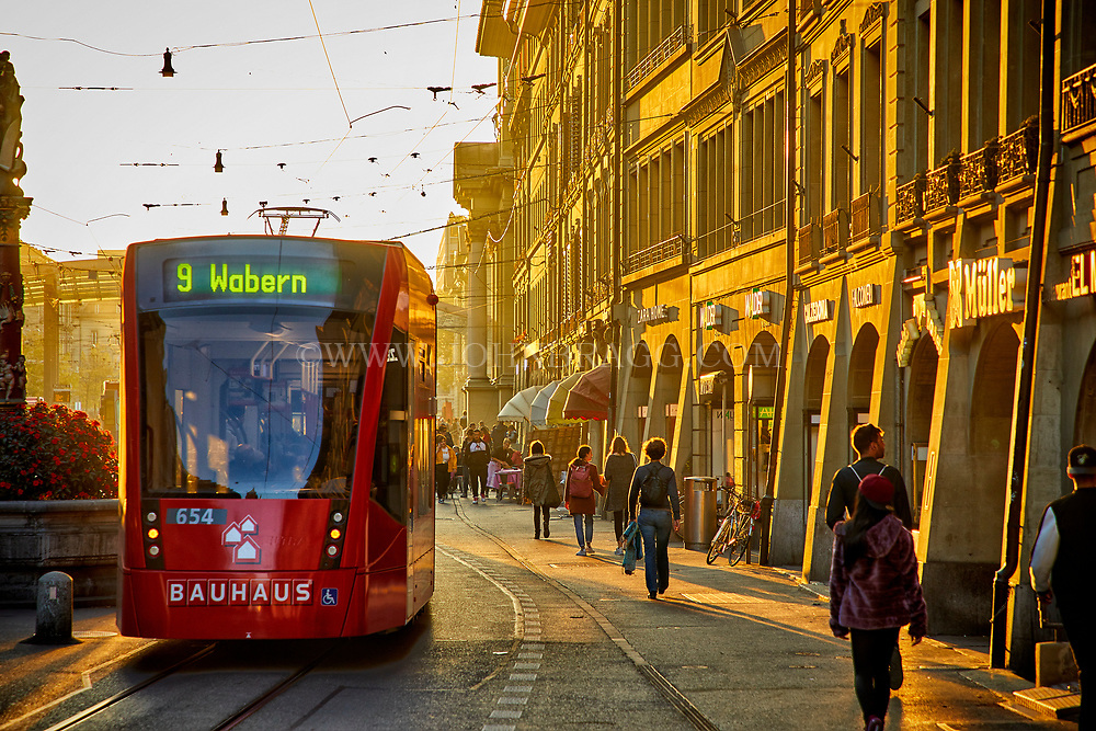 A tram travels down Spitalgasse as the sun sets on Bern, Switzerland.