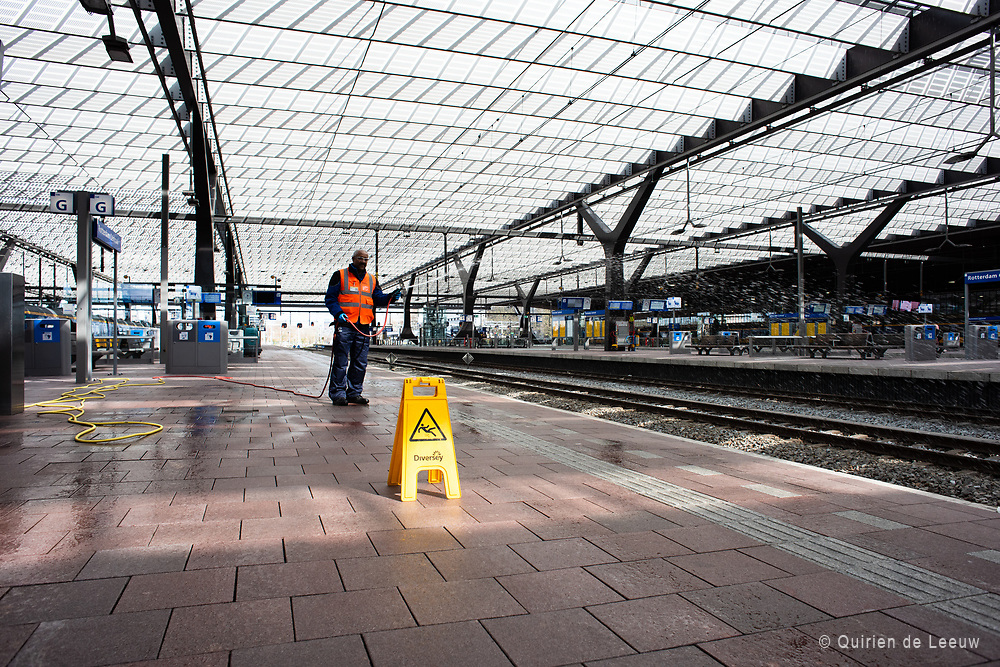 A facilityworker disinfects and cleans the station platforms during the Corona lockdown in a further empty station, Rotterdam Central Station.