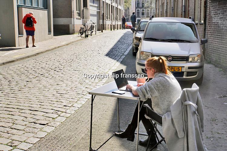 Nederland, Nijmegen, 15-4-2020   Een jonge vrouw zit aan een campingtafeltje voor haar huis in de benedenstad te werken . Het is mooi weer en buiten is het mogelijk rustiger als binnen nu iedereen vanwege het coronavirus zoveel mogelijk thuis moet werken en kinderen binnen moeten blijven . Foto: Flip Franssen
