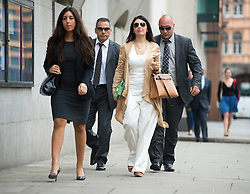 © London News Pictures. 21/08/2012. London, UK.  Nur Nadir (second from right) , wife of Cypriot businessman Asil Nadir arriving at The Old Bailey, in London accompanied by her security on August 21, 2012 where her husband is currently waiting for a jury to return a verdict on nine charges in the Polly Peck fraud case. The Old Bailey jury found Nadir, 71, guilty yesterday (Mon) of three counts of theft amounting to a total of more than £5.5 million.. Photo credit : Ben Cawthra/LNP