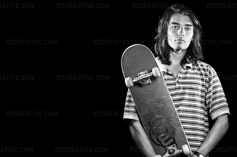Portrait of young a male in early twenties holding a skateboard on dark background.