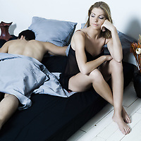 beautiful young caucasian couple in a bed with displeased  awake woman and man sleeping  on isolated white background
