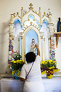 Woman showing her devotion to Sao Lazaro at an altar. Often the lines between Candomble and Catholicism are blurred. This is especially true with the Sao Lazaro event in late January in Salvador, Bahia, Brazil, the city which is known as the home of Candomble. Sao Lazaro represents healing and the sick.