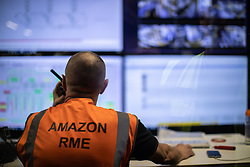 "© Licensed to London News Pictures . 04/12/2019. Manchester , UK . Staff monitor warehouse operations inside a unit at the centre of the warehouse . Inside the ""MAN1"" Amazon fulfilment centre warehouse at Manchester Airport in the North West of England . Photo credit : Joel Goodman/LNP"