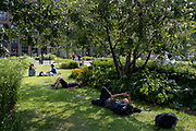Londoners relax and sleep on the grass opposite St Paul's Cathedral, on 21st July 2021, in the City of London, England.