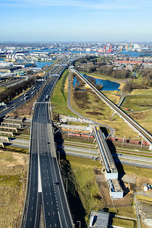 Nederland, Zuid-Holland, Rotterdam, 18-02-2015. A15 ter hoogte van knooppunt Benelux. A15 met Benneluxtunnel onder de Niuewe Maas aan de horizon, links Pernis met Shell raffinaderij.  Kolentrein op Betuweroute rijdt richting Maasvlakte en passeert leidingenviaduct.<br /> Motorway A15, connecting Port of Rotterdam with hinterland, harbours and container terminals.<br /> luchtfoto (toeslag op standard tarieven);<br /> aerial photo (additional fee required);<br /> copyright foto/photo Siebe Swart