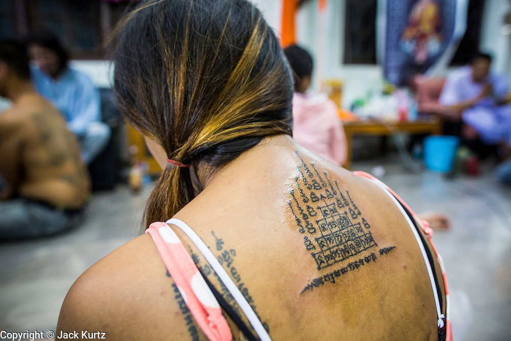 "22 MARCH 2013 - NAKHON CHAI SI, NAKHON PATHOM, THAILAND: A fresh Sak Yant tattoo on a woman's back at Wat Bang Phra. Wat Bang Phra is the best known ""Sak Yant"" tattoo temple in Thailand. It's located in Nakhon Pathom province, about 40 miles from Bangkok. The tattoos are given with hollow stainless steel needles and are thought to possess magical powers of protection. The tattoos, which are given by Buddhist monks, are popular with soldiers, policeman and gangsters, people who generally live in harm's way. The tattoo must be activated to remain powerful and the annual Wai Khru Ceremony (tattoo festival) at the temple draws thousands of devotees who come to the temple to activate or renew the tattoos. People go into trance like states and then assume the personality of their tattoo, so people with tiger tattoos assume the personality of a tiger, people with monkey tattoos take on the personality of a monkey and so on. In recent years the tattoo festival has become popular with tourists who make the trip to Nakorn Pathom province to see a side of ""exotic"" Thailand. The 2013 tattoo festival was on March 23.    PHOTO BY JACK KURTZ"