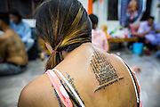 """22 MARCH 2013 - NAKHON CHAI SI, NAKHON PATHOM, THAILAND: A fresh Sak Yant tattoo on a woman's back at Wat Bang Phra. Wat Bang Phra is the best known """"Sak Yant"""" tattoo temple in Thailand. It's located in Nakhon Pathom province, about 40 miles from Bangkok. The tattoos are given with hollow stainless steel needles and are thought to possess magical powers of protection. The tattoos, which are given by Buddhist monks, are popular with soldiers, policeman and gangsters, people who generally live in harm's way. The tattoo must be activated to remain powerful and the annual Wai Khru Ceremony (tattoo festival) at the temple draws thousands of devotees who come to the temple to activate or renew the tattoos. People go into trance like states and then assume the personality of their tattoo, so people with tiger tattoos assume the personality of a tiger, people with monkey tattoos take on the personality of a monkey and so on. In recent years the tattoo festival has become popular with tourists who make the trip to Nakorn Pathom province to see a side of """"exotic"""" Thailand. The 2013 tattoo festival was on March 23.    PHOTO BY JACK KURTZ"""
