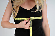 Body image - young woman measures her bosom