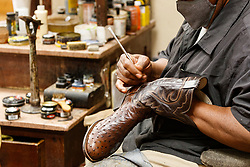 Man shining and polishing boots at M.L Leddy's Boots, Fort Worth Stockyards National Historic District, Fort Worth, Texas, USA.