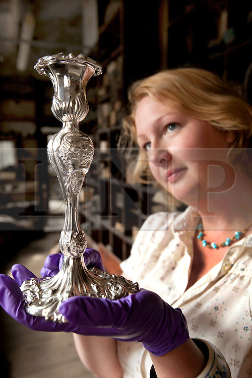 © licensed to London News Pictures. 19/05/2011. Birmingham, UK. English Heritage has stepped in and aquired JW Evans silver workshop to save it, and its contents, from developers. A family Silverware factory founded in 1881 in the heart of Birmingham's historic jewellery Quarter. Pictured, Beth Stanley, project conservator, holding a candlestick produced in the factory. Please see special instructions for usage rates. Photo credit should read Dave Warren/LNP