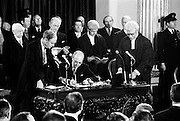 After the sudden death of Erskine Childers, Cearbhall O'Dalaigh was elected unopposed as fifth President of Ireland. Here, watched by Taoiseach Liam Cosgrave and Chief Justice Tom O'Higgins, he signs the oath of office. <br /> 19/12/1974