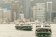 The Star Ferry crosses Victoria Harbor with the skyline of the Central District of Hong Kong. Star Ferry boats have been carrying passengers from Hong Kong Island to Kowloon and back since 1888.