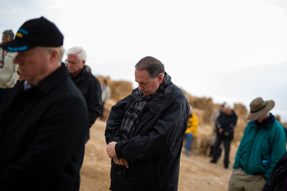 Former Arkansas governor Mike Huckabee (C) is seen as he prays together with a group of American Evangelical Christian tourists and pilgrims led by him, during a visit to the ancient hilltop fortress of Masada in the Judean desert in Israel, on February 19, 2015. The ancient ruined desert fortress on a wind-swept plateau overlooking the Dead Sea is seen by many as an emblem of Israel's fighting spirit, it is believed to be the place where close to a thousand Jewish rebels killed themselves and each other about two millennia ago, rather than surrender and fall into slavery under the Romans.