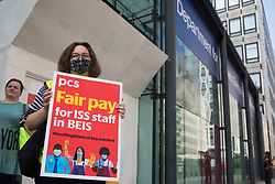 A PCS trade union rep stands on the picket line outside the Department for Business, Energy and Industrial Strategy (BEIS) on the second day of a 3-day strike by workers employed there by outsourced contractor ISS on 20th July 2021 in London, United Kingdom. The striking cleaners, security guards and other support staff are demanding an end to low pay, improved working conditions, bonuses for having worked through lockdown, annual leave from last year and a Covid return-to-work protocol.