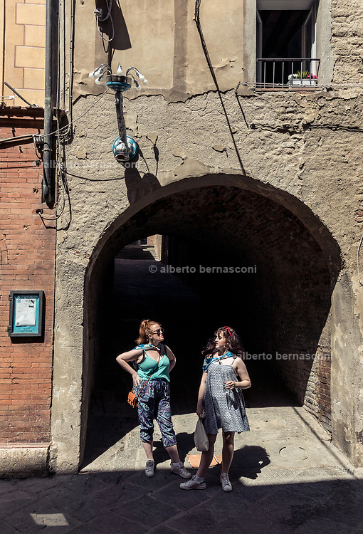 Italy, Siena, the Palio: daily life in the contradas, waiting for the final race, two girls from the Onda contrada