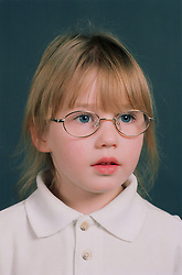 Portrait of young girl wearing glasses looking serious,