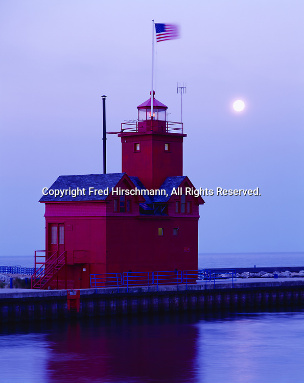 """Full moon setting at dawn beyond """"Big Red,"""" the Holland Harbor Lighthouse, originally built in 1907 and modified in 1936, Lake Michigan shore, Holland, Michigan."""