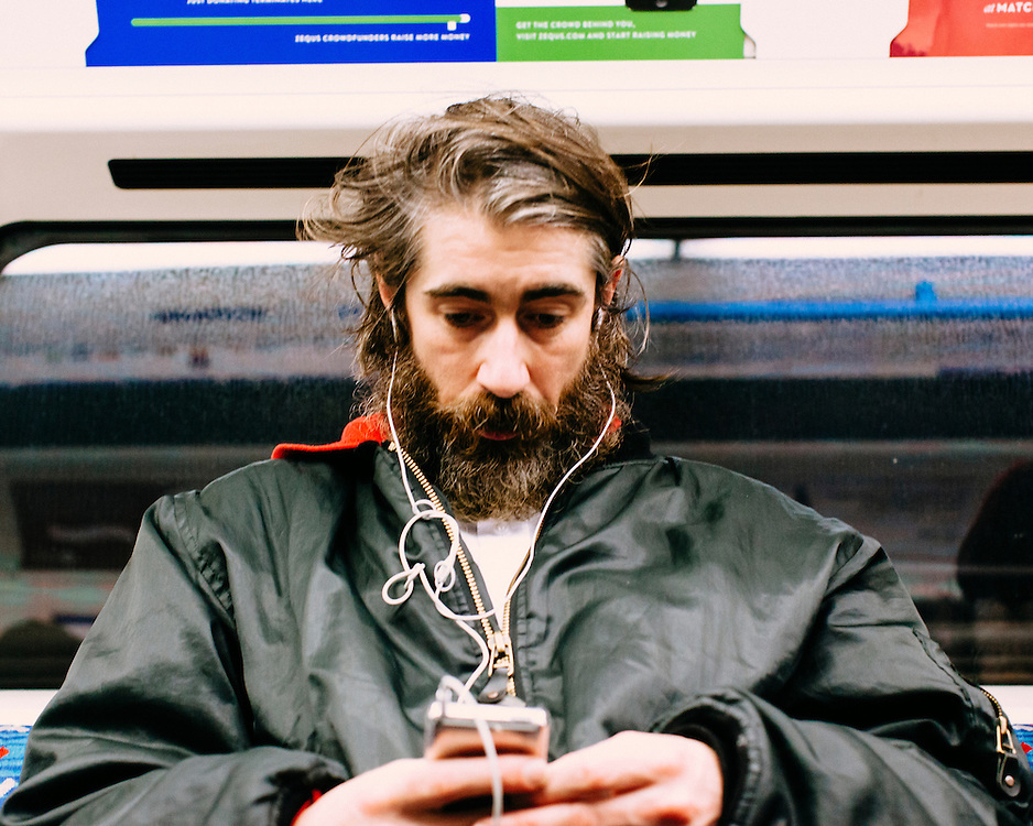 Portrait of a man on the London Underground listening to music