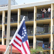 Residents watch from their balconies as protesters rally to end the stay at home order and open businesses and schools at Lake Eola on Saturday April 25, 2020 in Orlando, Florida.  Governor Ron DeSantis signed an executive order that restricts non-essential employees and businesses from opening and working. (Alex Menendez via AP)