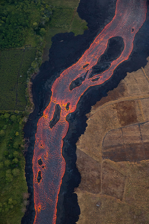 Kilauea's east rift zone: An incredible abstract created by this river of lava...With prevailing winds blowing from left to right, one can see the effect the heat and gases have upon vegetation. And, these islands in the middle of the channel, breakup the textured surface of the river, revealing more glow from the molten rock below.