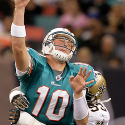 2009 September 03: New Orleans Saints defensive end Bobby McCray (93) hits Miami Dolphins quarterback Chad Pennington (10) as he throws during the first quarter of a preseason game between the Miami Dolphins and the New Orleans Saints at the Louisiana Superdome in New Orleans, Louisiana.