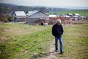 Rudolf (52) walking up a little hill with the  construction side of the familie's selfconstructed buildings in the back. After one year of construction (04/2014) the familie's are already able to life in the houses. They joined a micro loan program in Rankovce.