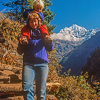 Carrying her 3-year old son Ben, Meredith Wiltsie treks in the Khumbu Region of Nepal, with Mount Kusum Khangri in background.