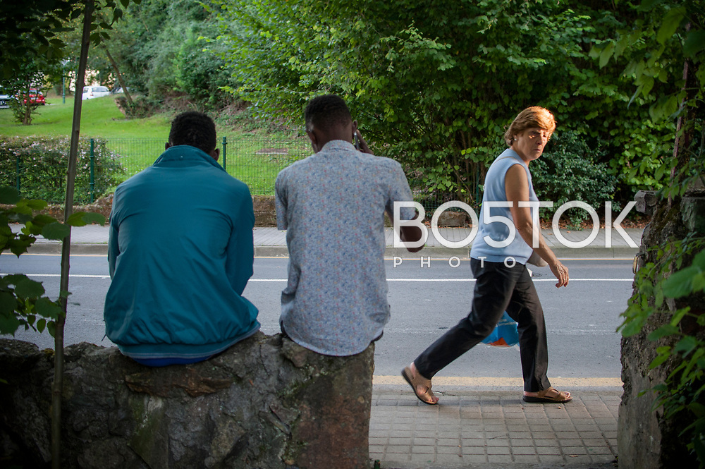 A woman passes by Lakaxita while two African migrants talk to each other. Irun (Basque Country). August 30, 2018. Lakaxita is a self-managed socio-cultural space located in an occupied house, where volunteers have created a hosting network for migrants in transit who have already completed the 5-day period that can remain in public resources. This group of volunteers is avoiding a serious humanitarian problem Irún, the Basque municipality on the border with Hendaye. As the number of migrants arriving on the coasts of southern Spain incresead, more and more migrants are heading north to the border city of Irun. (Gari Garaialde / Bostok Photo)
