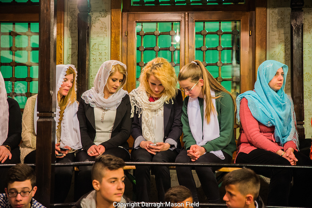 Young women look at their phones as they wait for the Zikr to start.