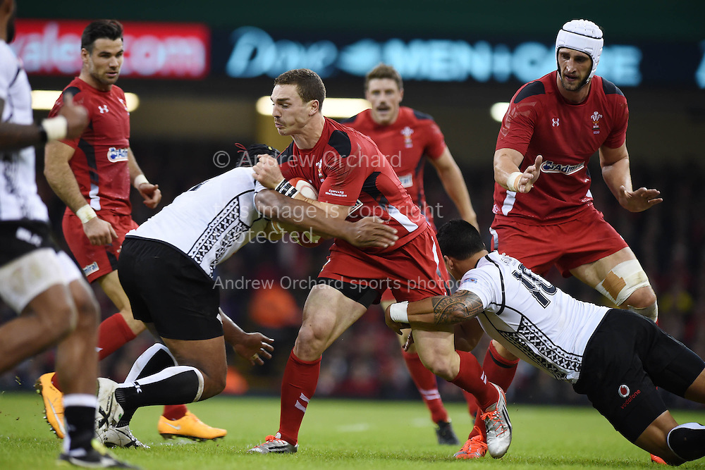 George North of Wales is tackled. Dove Men series 2014, autumn international rugby, Wales v Fiji at the Millennium Stadium in Cardiff, South Wales on Saturday 15th November 2014.<br /> pic by Andrew Orchard, Andrew Orchard sports photography.