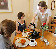 Owner Jane Muscroft (right) waits on customers Ella Schultz, 12 at left, and her mother Kristin Schultz, both of St. Louis at Muscroft's Queen's Cuisine Tea Room in Edwardsville. Muscroft is from England and has many original recipes for patrons of her new business, which has been open about a month. Ella ordered the Cornish Pasty with Sarah's Tomato & Basil soup, while her mother ordered the Little Bit of Everything lunch special. Both had blackberry sage tea.