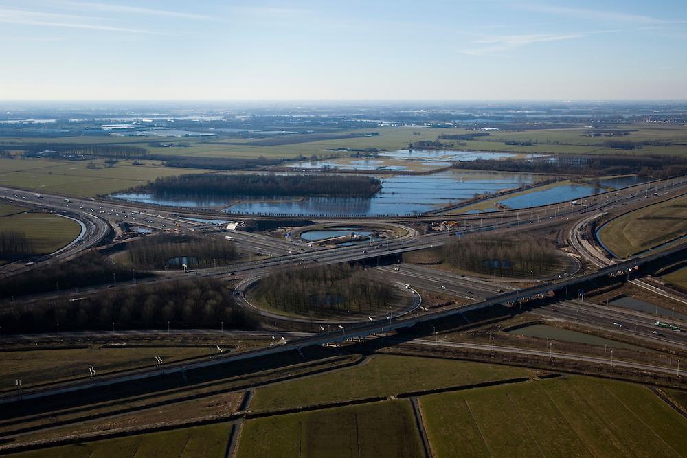 Nederland, Gelderland, Gemeente Neerijnen,  07-03-2010; Knooppunt Deil, verkeersknooppunt in de vorm van een klaverblad, kruising A15 (links-rechts) met A2 (diagonaal). Het knooppunt wordt verruimd en de A2 verbreed en er worden nieuwe bomen (populieren) geplant. In de 'oksel' van het knooppunt het natuurreservaat Het Broek. .Deil junction, crossroads A15 (left-right) with A2 (diagonal). The node is expanded and the A2 widened, new poplar trees are being planted. In the 'armpit' of the junction thenature reserve Het Broek..luchtfoto (toeslag), aerial photo (additional fee required).foto/photo Siebe Swart