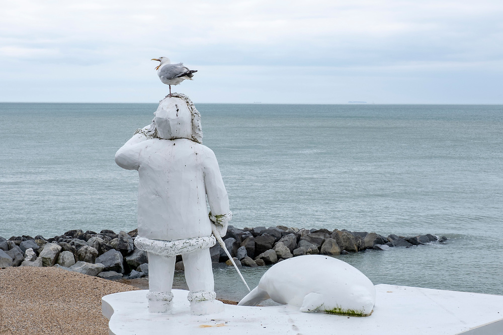 A seagull sits on The Ledge by Bill Woodrow is a sculpture right on Folkestone Seafront suggesting the demarcation of the rising water level resulting from the disappearing polar ice caps, depicting a human figure and a seal standing on thin ice, on the 15th of July 2021, Folkestone, United Kingdom. The artwork builds on the work from previous triennials making Folkestone the biggest urban outdoor contemporary art exhibition in the UK.  (photo by Andrew Aitchison / In pictures via Getty Images)