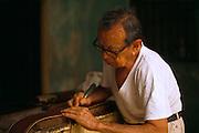 Portrait of saddle maker hammering leather strap.