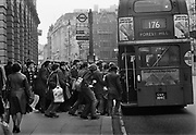 Passengers rushing for a 176 bus in front of Sommerset House, Aldwich. Coming and Going is a project commissioned by the Museum of London for photographer Barry Lewis in 1976 to document the transport system as it is used by passengers and commuters using public transport by trains, tubes and buses in London, UK.