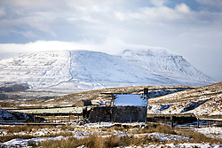 © Licensed to London News Pictures. 10/11/2016. Ingleton UK. Picture shows a derelict farm building in the shadow of the snow covered Whernside mountain in the Yorkshire Dales. Photo credit: Andrew McCaren/LNP