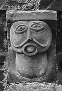 The Stone Bestiary - Black and white photo art print of Norman Romanesque exterior corbel no 49  - sculpture of  an alien like chinless bald headed figure. Its perfectly round mouth is filled with a ball like object and may be a moral warning about talking too much. The Norman Romanesque Church of St Mary and St David, Kilpeck Herefordshire, England. Built around 1140 .<br /> <br /> Visit our LANDSCAPE PHOTO ART PRINT COLLECTIONS for more wall art photos to browse https://funkystock.photoshelter.com/gallery-collection/Places-Landscape-Photo-art-Prints-by-Photographer-Paul-Williams/C00001WetsxVxNTo .<br /> <br /> By Photographer Paul E Williams