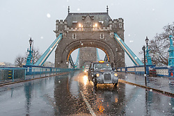 © Licensed to London News Pictures. 10/12/2017. London, UK. A taxi crosses Tower Bridge during heavy snow fall. Heavy snow has fallen across the UK this morning. Photo credit: Vickie Flores/LNP
