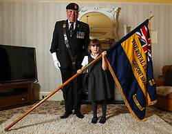 Mollie Stonelake, seven, holds a full-size standard from the Torpoint & District Branch of the Royal British Legion alongside branch chairman Colin Prideaux, in her family home in Torpoint, Cornwall. Mollie went on her first parade aged five and will carry a specially-made miniature standard in a service on Sunday in her home town of Torpoint in Cornwall.
