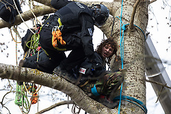 Steeple Claydon, UK. 24 February, 2021. Thames Valley Police officers acting on behalf of HS2 Ltd use a cherry picker to evict an activist opposed to the HS2 high-speed rail link from ancient woodland known as Poors Piece. Thames Valley Police stepped in to replace National Eviction Team bailiffs. The activists created the Poors Piece Conservation Project in the woodland in spring 2020 after having been invited to stay on the land by its owner, farmer Clive Higgins.