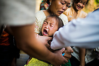 Gpa Yia cries during her JE vaccination at the campaign in Khon Kahndone Village, Xieng Khouang province, Laos. Her eldest brother died of JE, and now the family is being vaccinated.