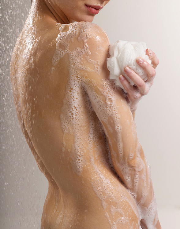Rear view of a woman soaping her beautiful and graceful nude torso and arm in shower