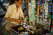 "A Paan wallah making paan in Old Delhi, India. <br /> Paan consists of chewing Betel leaf (Piper betle) combined with the areca nut. It is chewed as a palate cleanser and a breath freshener. It is also commonly offered to guests and visitors as a sign of hospitality and as an ""ice breaker"" to start conversation. It also has a symbolic value at ceremonies and cultural events in south and southeast Asia. Paan makers may use mukhwas or tobacco as an ingredient in their paan fillings. Although most types of paan contain areca nuts as a filling, some do not. Other types include what is called sweet paan, where sugar, candied fruit and fennel seeds are used."