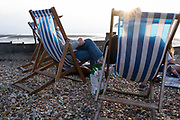 Staycationers sit in deck chairs on beach shingle, to enjoy the calm of a low-tide evening sunset, on 25th July 2021, in Whitstable, Kent, England.