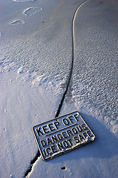 A sign warning of the dangers of the ice lays on a large crack in the ice on a lake