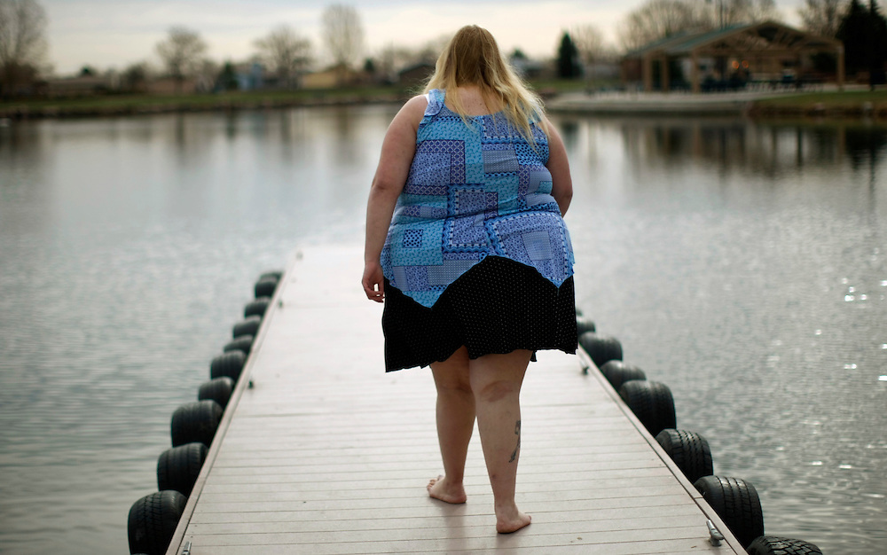 Gabi Jones walks along a pier during a photo shoot for her website in a suburb of Denver April 12, 2010.  Jones (not her real name) weighs 502 pounds and is an advocate of size acceptance, using her modeling to inspire those who have low self-esteem.  REUTERS/Rick Wilking  (UNITED STATES)