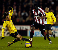 Photo: Jed Wee.<br />Sheffield United v Arsenal. The Barclays Premiership. 30/12/2006.<br /><br />Sheffield United's Christian Nade (R) skips past the challenge of Arsenal's Tomas Rosicky.