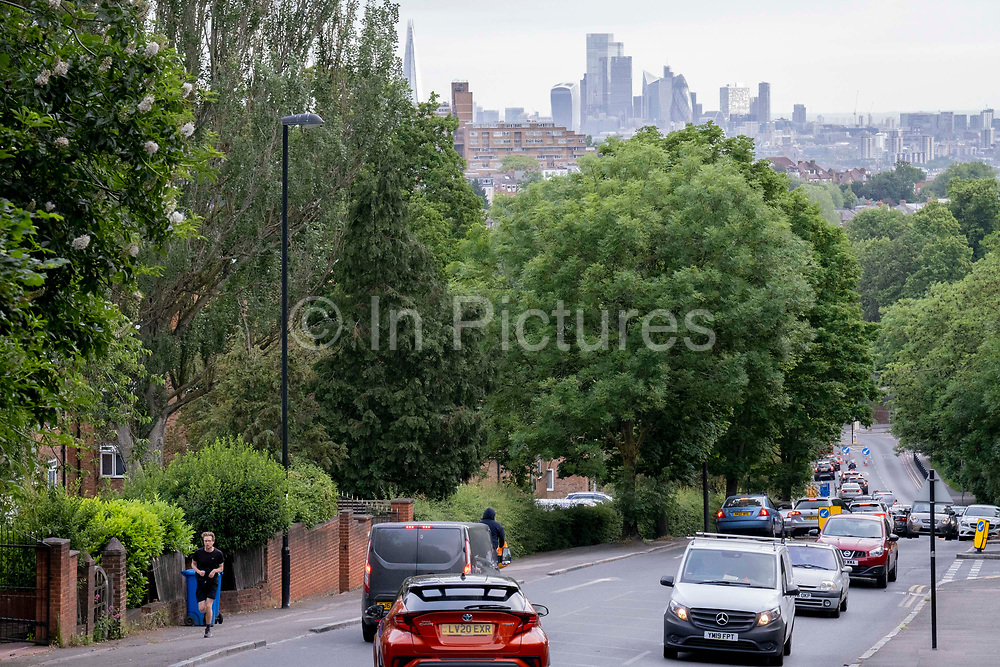 With the skyscrapers of the City of London, the capitals financial district, in the distance, a runner climbs uphill and rush-hour traffic builds at the bottom of Sydenham Hill, on 15th June 2021, in south London, England.